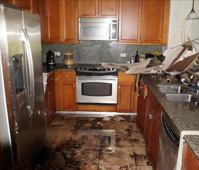Kitchen with water damage on the floor and messy cabinetry.